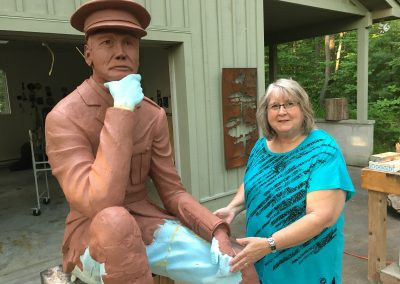 065 Pam putting a piece on Sam Sharpes Statue